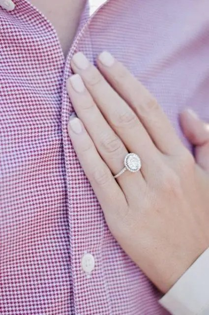 a classic round-shaped diamond ring with a thin halo and a thin band in white gold