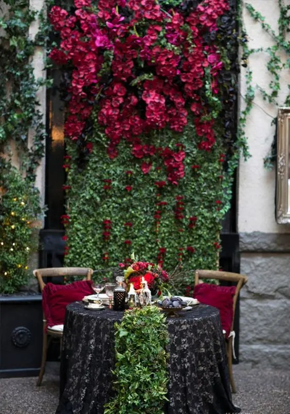 a living wall with lush black and burgundy blooms and a matching greenery runner on the table
