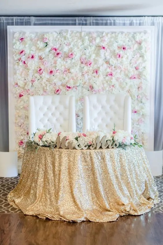 a floral wall of cream and pink blooms in a frame for a refined glam wedding