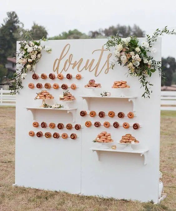 an elegant outdoor donut wall with shelves, calligraphy and fresh blooms for a chic wedding