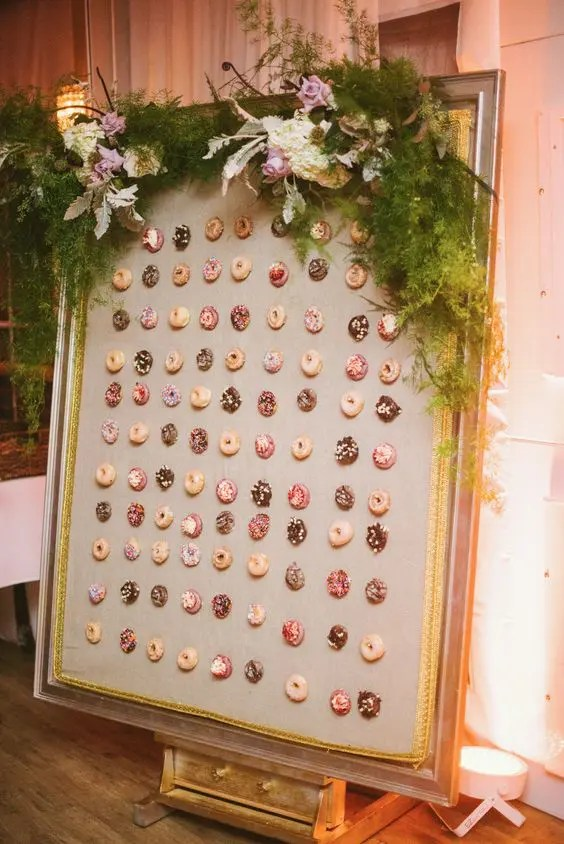 a chic framed donut wall with lush greenery and blooms looks liek a tasty artwork