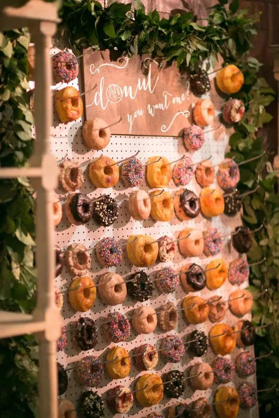 a pegboard donut wall decorated with fresh greenery garlands