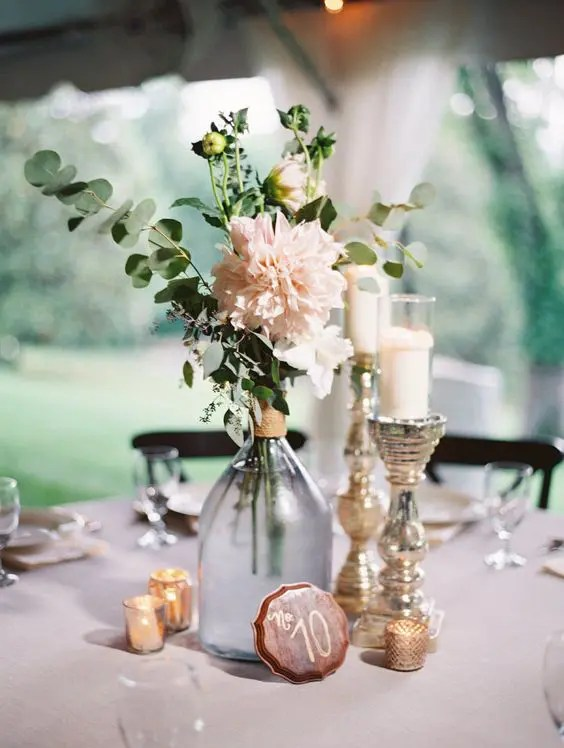 an elegant centerpiece with greenery, blush blooms, candles and a cute table number
