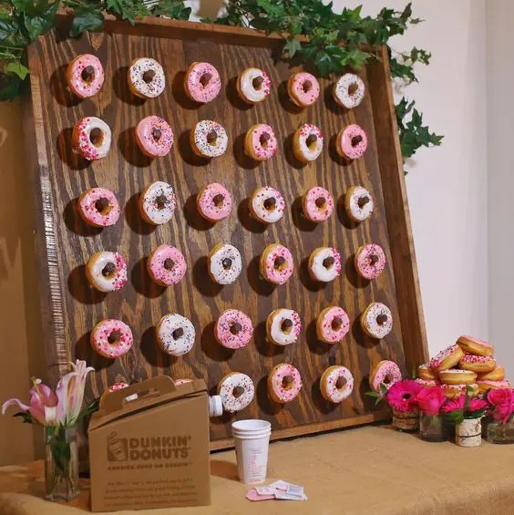 a mini donut wall decorated with fresh greenery and with fresh blooms around