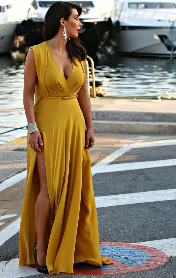 a mustard maxi dress with a deep V-neckline and a side slit, a small and thin leather belt