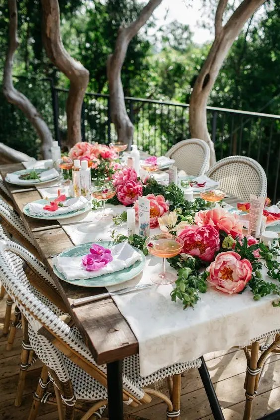a beautiful and simple tablescape with a greenery and peony table runner, blooms on each setting and neutral textiles