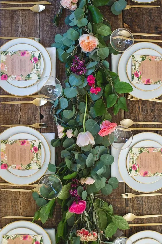 a fresh floral and greenery garland, floral menus and gold flatware for a cute garden-inspired tablescape