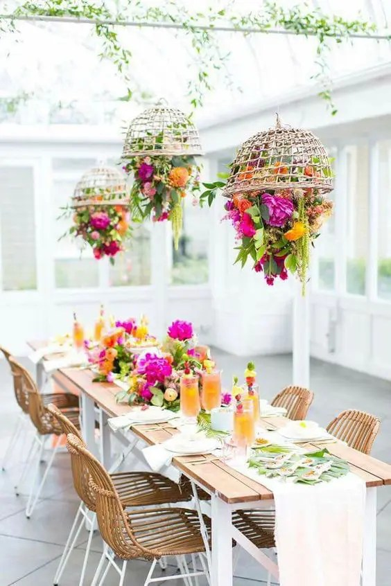 if the weather is bad, go to the sunroom and rock much greenery, super bold blooms and wicker touches to make everyone feel outdoors