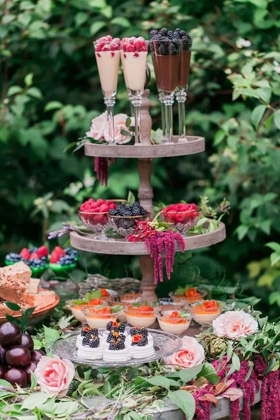 gorgeous desserts, cupcakes, berries and souffle served on a stand with flowers and greenery garlands to give it a garden feel