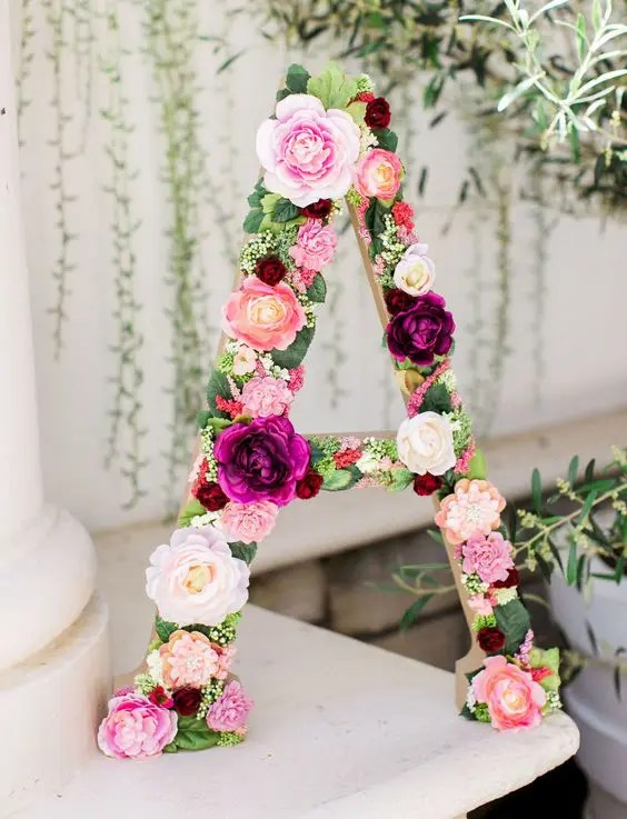 make a cool shower decoration using a letter and some faux greenery and blooms to attach to it