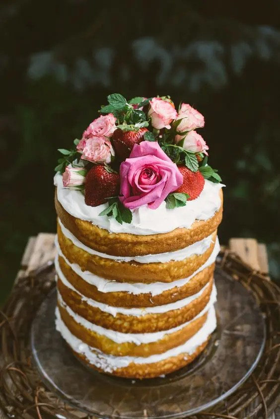 a gorgeous tall naked cake with whipped cream, fresh strawberries and pink roses on top for a garden bridal shower
