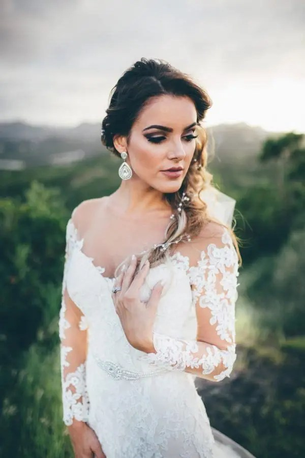 a glam bride wearing an embellished sash and oversized glam earrings with an off the shoulder dress