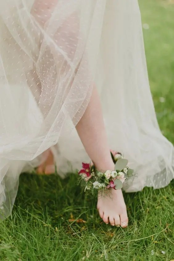 a floral anklet with plum-colored blooms and greenery for a garden bride