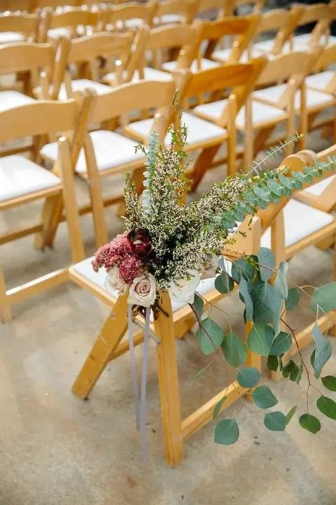a lush floral arrangement with herbs and eucalyptus, burgundy and blush blooms