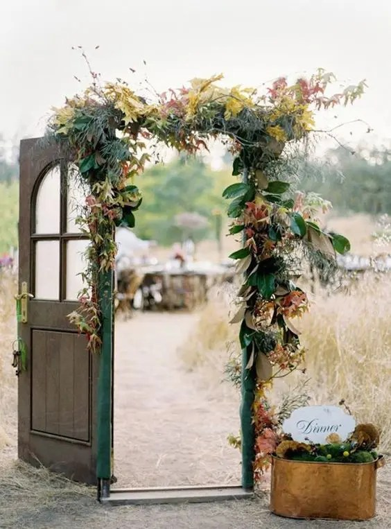 Picture Of a wedding gate decorating with magnolia and colorful fall     Picture Of a wedding gate decorating with magnolia and colorful fall leaves  and some grasses and an emerald ribbon