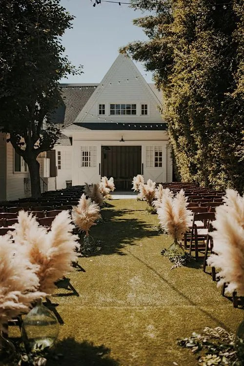 pampas grass in glass vases to line up the aisle for a fall boho wedding