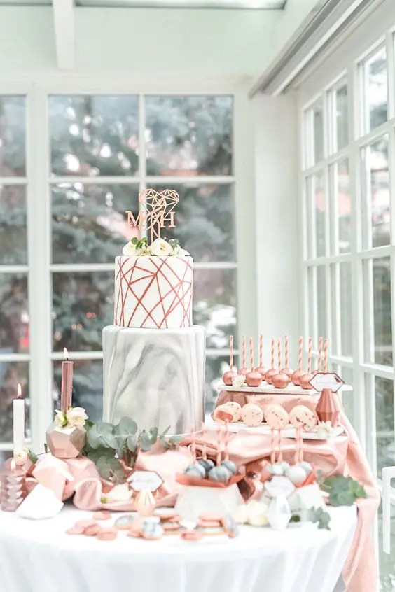 a modern geometric dessert table with copper and marble touches and faceted items