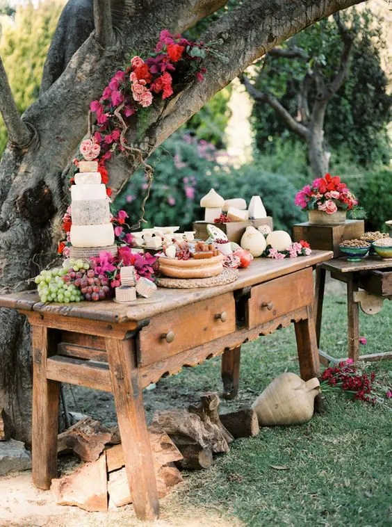 an outdoor dessert, fruit and cheese table decorated with lush and bright florals
