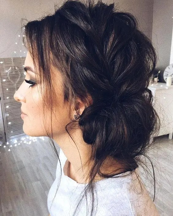 a messy side braided updo with locks down is a comfy and chic option