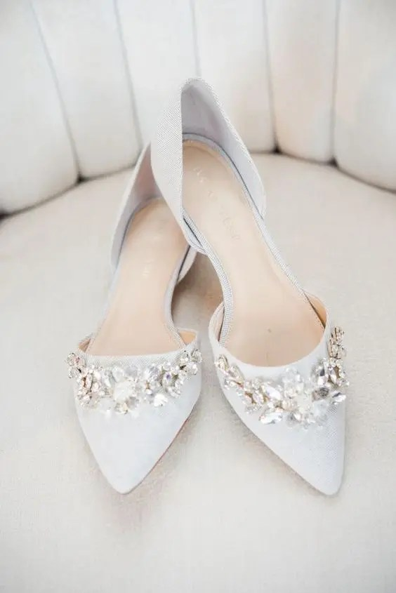 off-white pointed toe flats with large floral embellishments for a romantic feel
