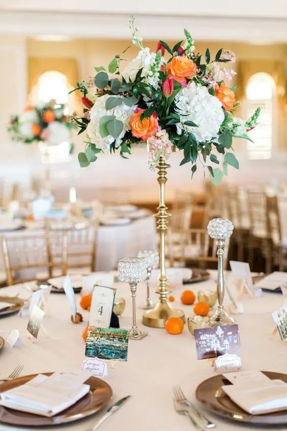 a cute tall wedding centerpiece with white hydrangeas, orange roses and greenery and citrus on the table