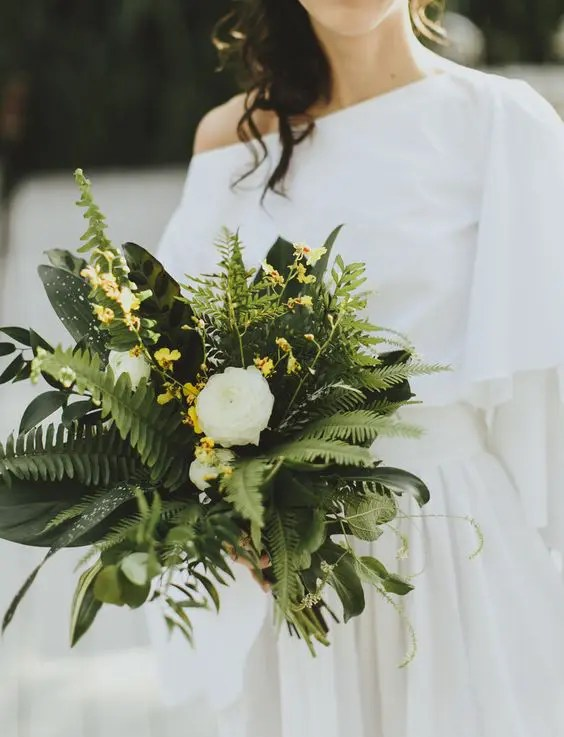 a chic wedding bouquet with ferns, leaves and white and yellow blooms is a unique idea