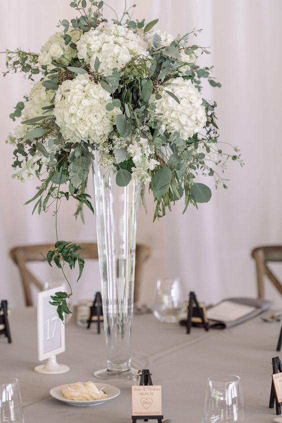 a lush floral centerpiece of eucalyptus and white hydrangeas in a tall glass vase
