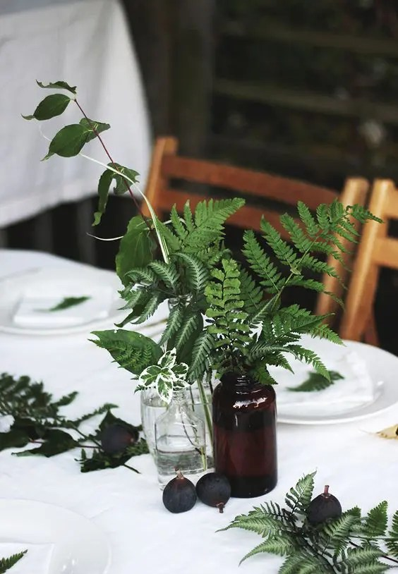 a table setting done with figs and ferns and foliage in vases and bottles for fresh fall feel