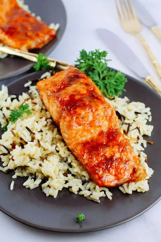 apricot glazed salmon served with rice and fresh herbs as an alternative to meat