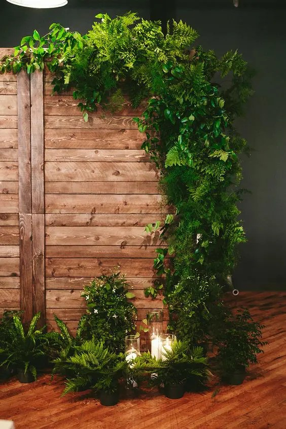 a wedding backdrop of wood decorated with ferns and other greenery, with candles around