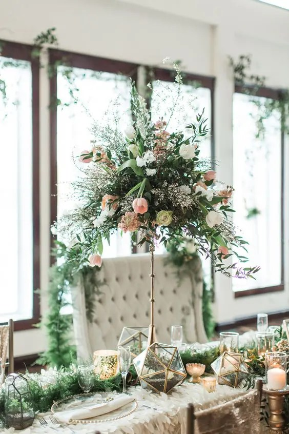 a textural centerpiece of white and blush blooms with textural cascading greneery on a tall brass stand