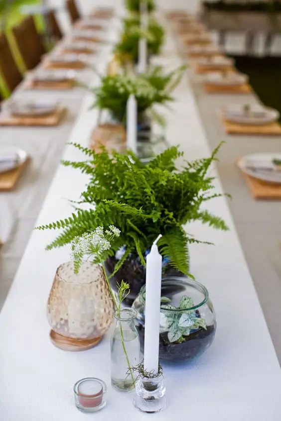 simple fern centerpieces, candles, colored glass and potted foliage for a woodland-inspired wedding tablescape