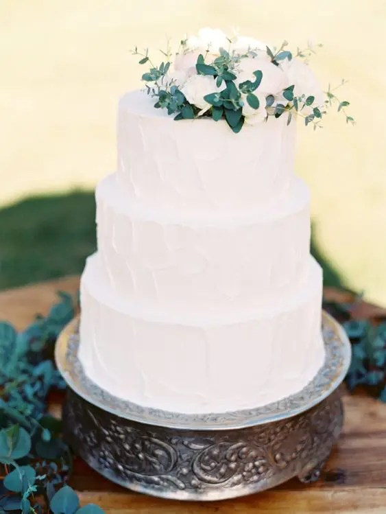 a natural and textural white wedding cake with white and blush blooms and greenery on top
