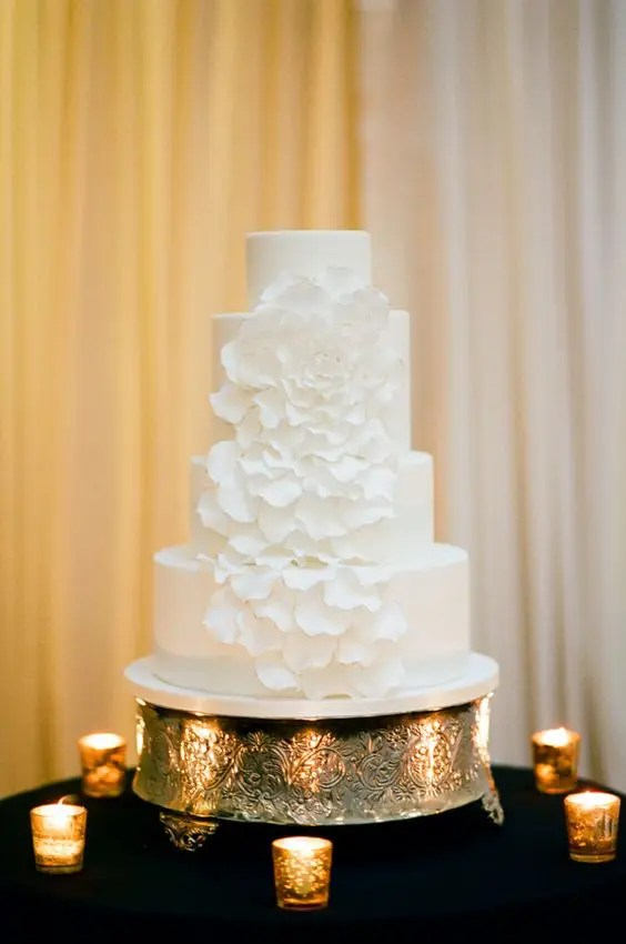 a plain white wedding cake decorated with a large white sugar flower, the petals are cascading for a whimsy touch