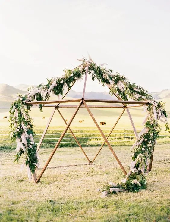 a geometric altar decorated with greenery and pampas grass is amazing for a boho chic or mid-century wedding