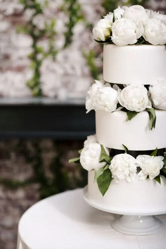 a trio of minimalist plain wedding cakes served with white peonies is an elegant modern wedding idea