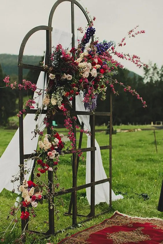 a forged frame decorated with airy fabric and lush colorful blooms plus a Persian rug for a dreamy outdoor ceremony