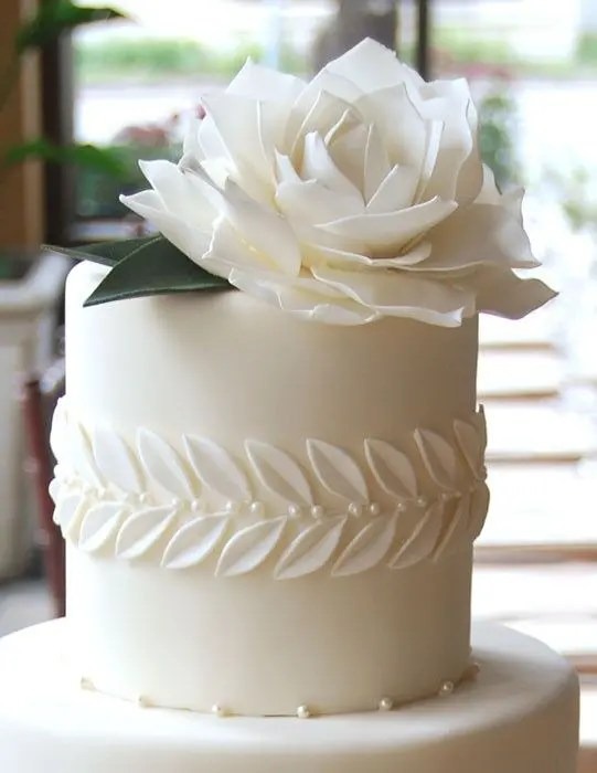 a white wedding cake with sugar leaves and a giant flower plus edible pearls is pure elegance with a modern twist