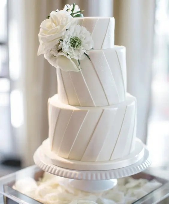 a striped white wedding cake topped with white blooms is a cool and timeless idea to rock