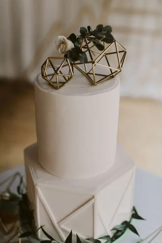 a white geometric wedding cake with gold himmeli toppers and greenery and white blooms