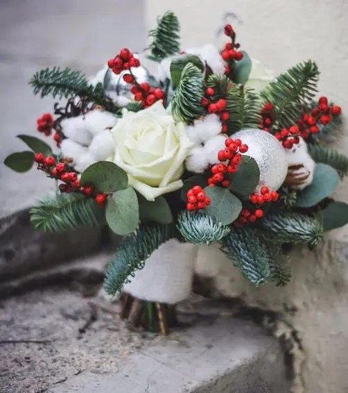 a Christmas wedding bouquet with holly berries, cotton, white roses and evergreens plus an ornament