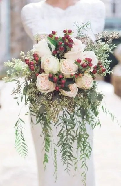 a holiday wedding bouquet with cascading greenery, blush roses, eucalyptus and holly berries
