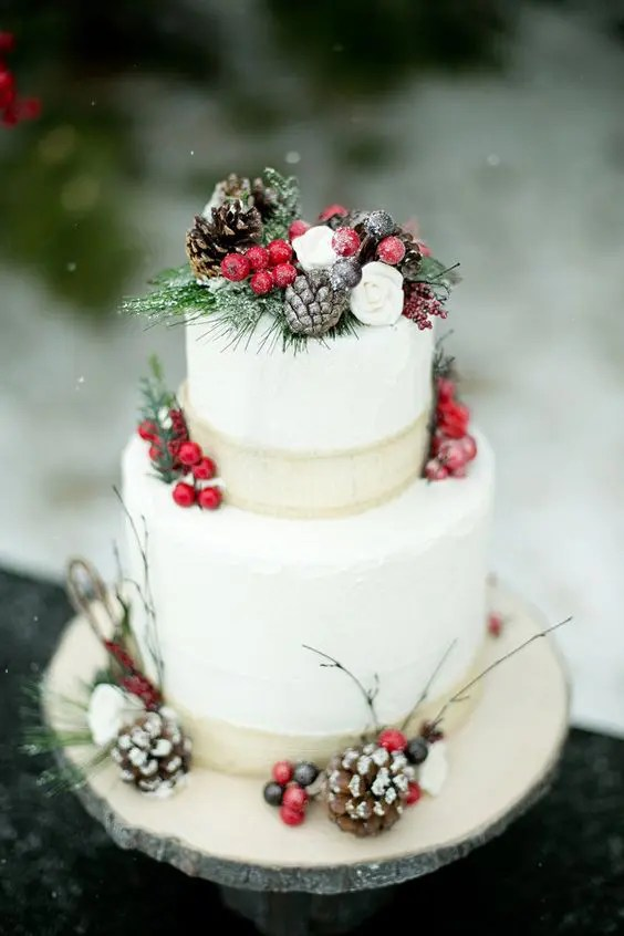 a Christmas wedding cake topped with fake greenery, berries, pinecones and burlap ribbons for a snowy feel