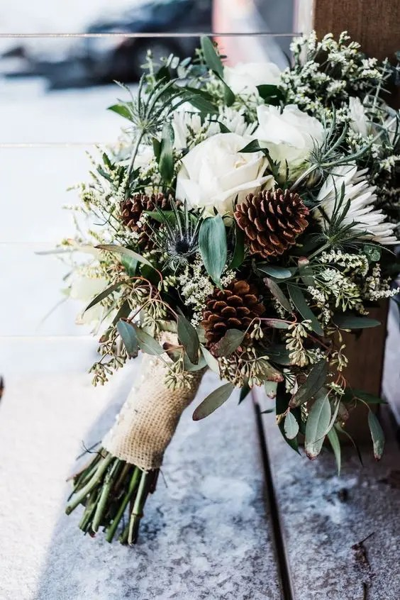 a rustic winter wedding bouquet with lots of greenery, pinecones, white blooms and a burlap wrap