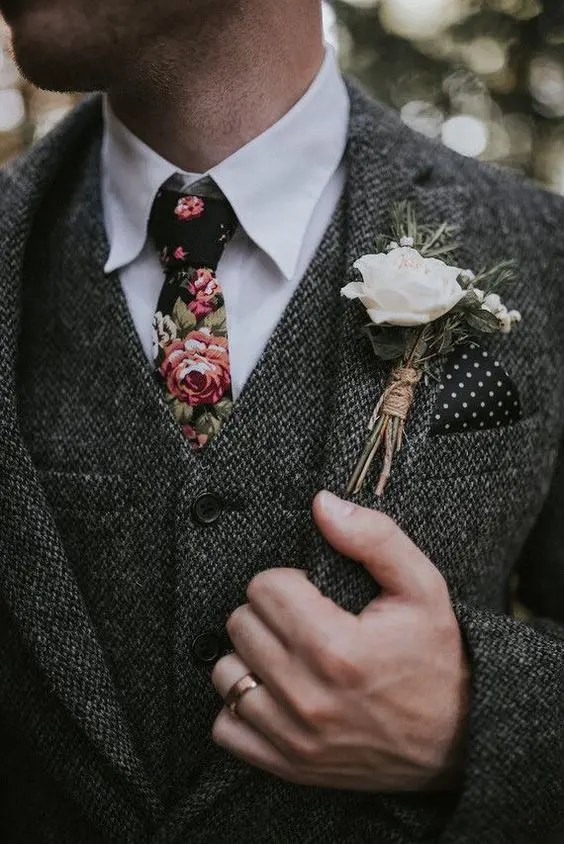 a grey three-piece wedding suit, a white sirt and a moody floral tie for a trendy winter groom look