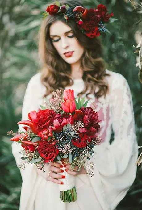 a winter wedding bouquet with red peonies and roses, chili peppers, and berries for Christmas