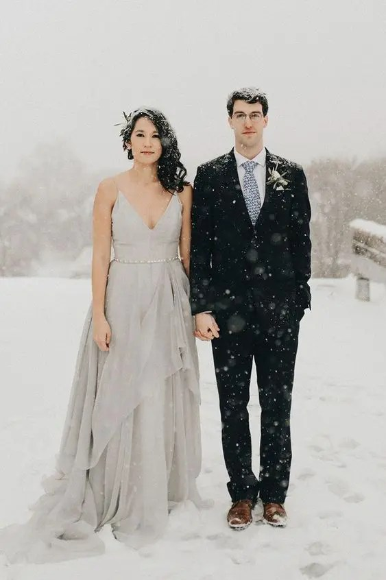 a grey wedding dress with a layered skirt, a V-neckline and an embellished sash for a modern romantic look