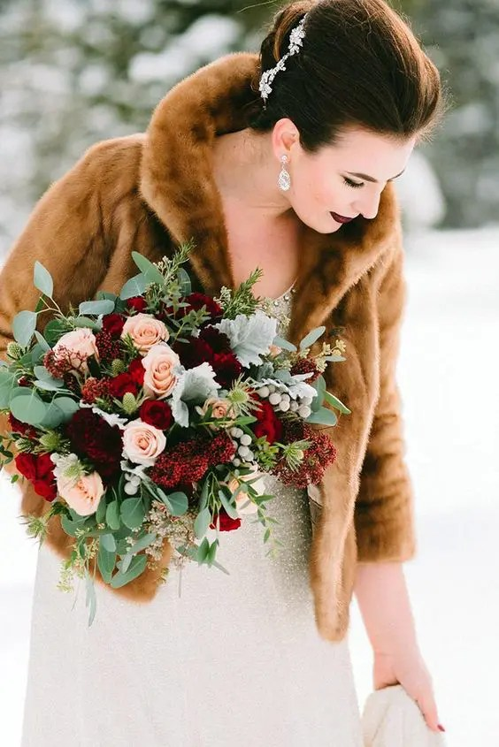 a winter wedding bouquet of burgundy, red and blush blooms plus pale greenery and eucalyptus