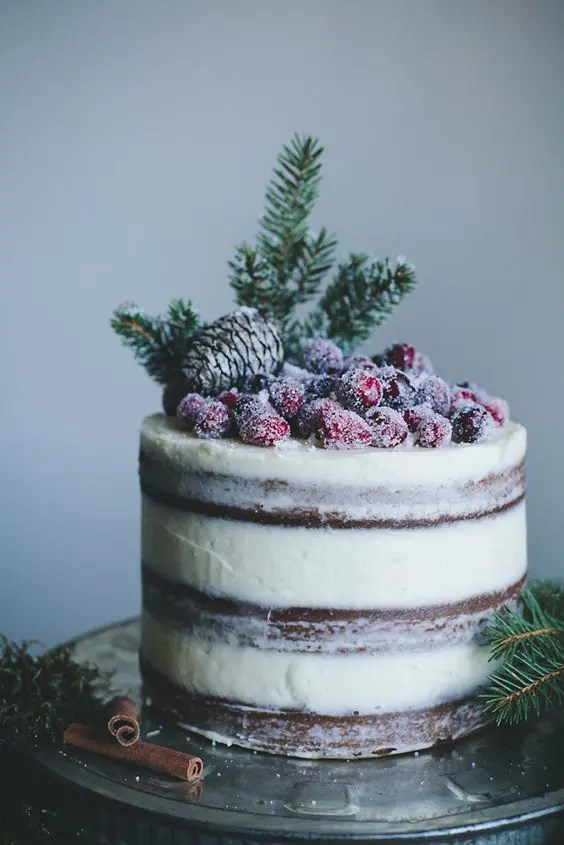 a semi naked wedding cake topped with a pinecone, evergreens and sugared berries for Christmas