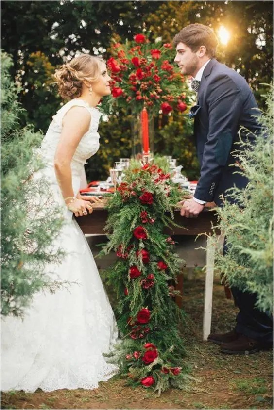 a classic lush evergreen table runner with red roses and a matching red rose centerpiece plus red candles